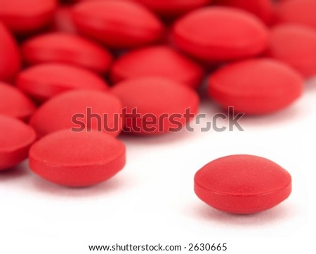 Pile of many small red pills, with one isolated on white in the front.