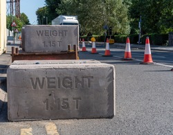 Pile of massive slabs of concrete create an immovable security barrier obstructing assess to the roadside. Each block is marked with 'Weight 1.15 T'. Yellow no parking lines lead to the first block.