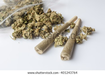 Pile of medical cannabis dried buds scattered from nylon package and two marijuana joints on white background from side