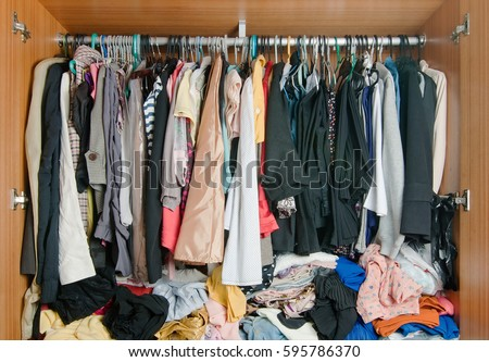 Pile of messy clothes in closet. Untidy cluttered woman wardrobe.