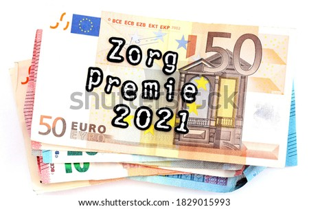 Pile of money with the dutch words zorg premie 2021 which means health insurance premium 2021  Foto stock ©