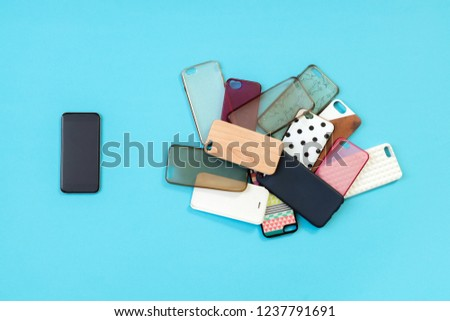 Pile of multicolored plastic back covers for mobile phones on blue background with a phone on the side #1237791691