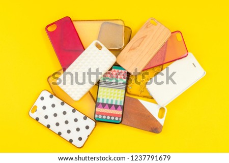 Pile of multicolored plastic back covers for mobile phones on yellow background #1237791679