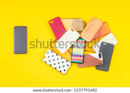 Pile of multicolored plastic back covers for mobile phones on yellow background with a phone on the side #1237791682