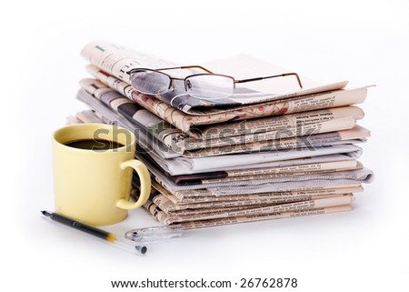 Pile of newspaper with coffeecup, pencil and glasses