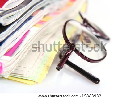 pile of newspapers and eyeglasses
