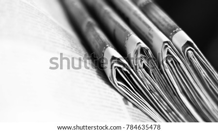 Pile of newspapers. Folded and stacked daily papers with news. White pages with headlines, articles and photos. Selective focus on journals, blurred background texture                #784635478
