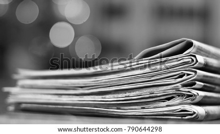 Pile of newspapers. Folded and stacked pages with news, headlines, articles and photos on the wooden table. Daily papers under Christmas tree in the morning. Selective focus, blurred background  #790644298