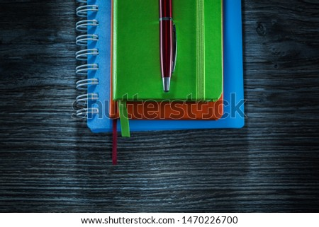 Pile of notepads pen on wooden board.