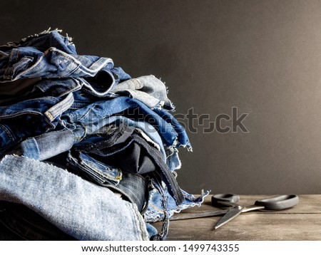 Pile of old blue jeans ready for recycling in the circular economy. Scissors on a wooden table, dark background. Room for text.
