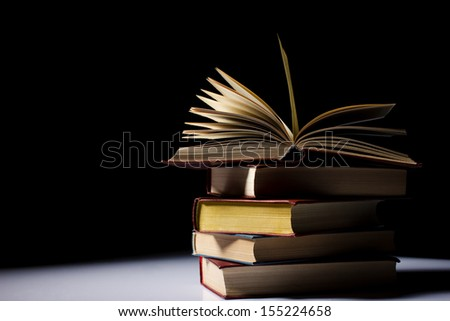 pile of old books on light table, one book opened,  black background