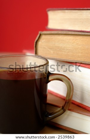 Pile of old books with covers and white pages with red background and a mug or cup of coffee close up