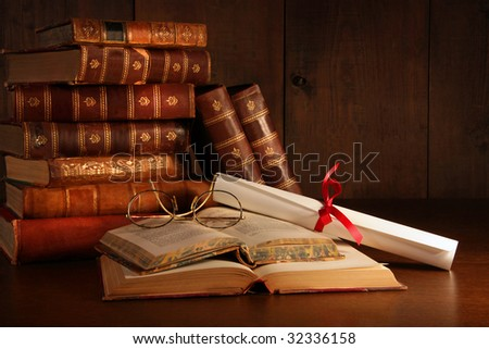 Pile of old books with reading glasses on desk