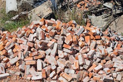 Pile of old red bricks on a demolition site