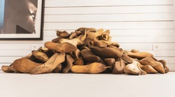 Pile of old, retro, wooden shoe molds lying on the white floor, against wooden plank wall