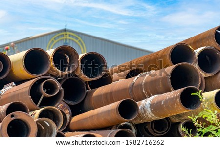 Pile of old rusty round metal industrial pipe. Steel pipe stack at warehouse of factory. Industrial material. Metal corrosion. Stack of rusty tube. Old iron pipe at warehouse. Metal pipe industry.