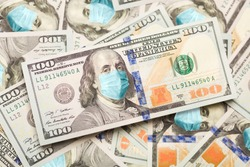 Pile of One Hundred Dollar Bills With Medical Face Mask on Face of Benjamin Franklin.