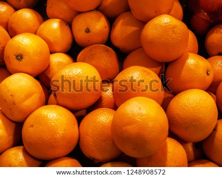 Stock Photo Pile of oranges closeup photo. Many oranges background. Fresh fruits in market display. Heathy vegetarian diet. Shiny oranges wallpaper. Natural harvest for Christmas or Chinese New Year party.