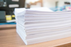 Pile of overwork paper documents or reuse printout on office desk stacked concepts of reduce recycle and messy desk.