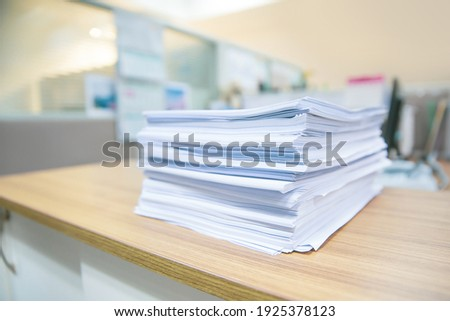 Pile of overwork paper documents or reuse printout on office desk stacked concepts of reduce recycle and messy desk. Stock photo ©