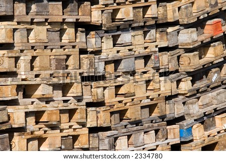 Pile of palettes - recyclable material. Logistics and ecology background.