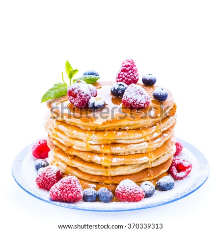 Pile of pancakes with blueberries and raspberries sprinkled with icing sugar and poured on with honey for breakfast on white background #370339313