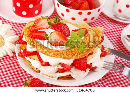 pile of pancakes with strawberries and whipped cream