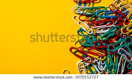 Pile of paperclips on a yellow background