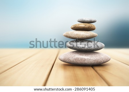 Pile of pebble stones for oriental spa massage therapy and alternative medicine on wooden planks outdoor with selective focus effect