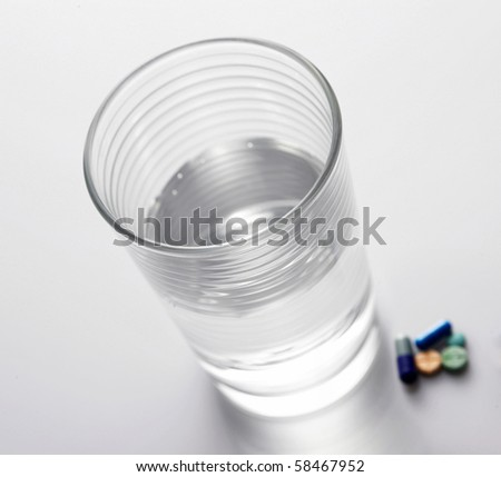 Pile of Pills next to Glass of water, isolated on plain background. #58467952