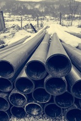 Pile of plastic pipes on construction site ready to be used.