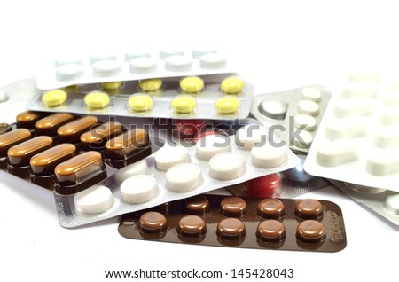 pile of plates with pills on a white background
