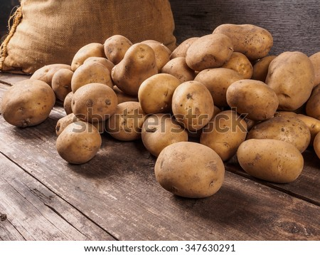 Photo of  Pile of potatoes lying on wooden boards with a potato bag in the background
