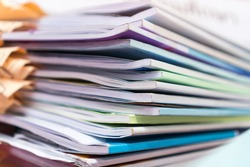 Pile of publication books or documents report papers waiting be managed on desk in busy office. Concept of workload in business finacial paperwork