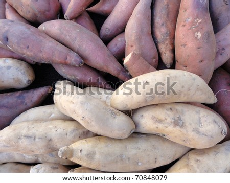 Pile of Purple and White Yams for sale at a market.