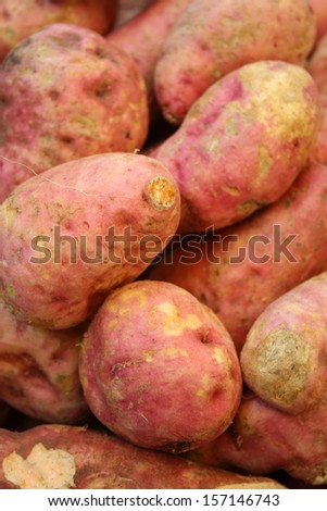 pile of raw sweet potato for retail sale in local market