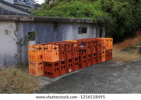Pile of red and orange plastic crates or boxes for bottle of drink at wayside near warehouse  #1256518495