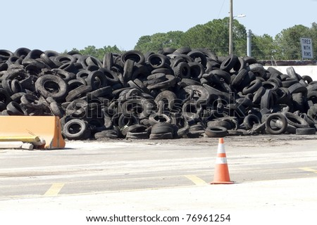 "Pile of rimless tires on ""Recycle Alley"" at a landfill. The sign for tires with rims can be seen."