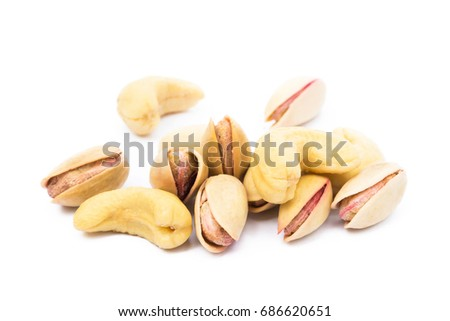 Pile of roasted pistachios and cashew isolated on white background #686620651