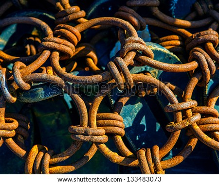 Pile of rusted chains at a boatyard.