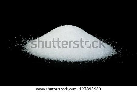 Pile of salt on black background .