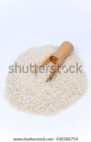 Pile of sesame with wooden spoon isolated over white background. #430386754