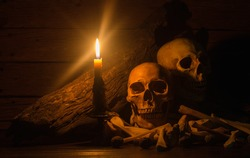 Pile of skulls and bones in the candle light,Halloween concept, still life and dim light