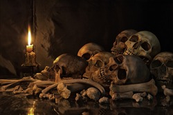 Pile of Skulls and bones on the reflection floor and old dirty wall have Lighting by candlelight / Still Life Image and dim light and adjustment color for background