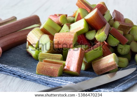 Pile of sliced rhubarb and knife on a blue tea towel with a grey wood background