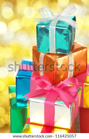 Pile of small gifts on gold blurry lights background.(vertical) Many gifts wrapped colorful metallic paper and ribbon.
