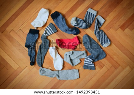 Pile of socks. Missing red sock. Search for the missing sock. Socks on wooden floor. Pairs of socks but one is missing.