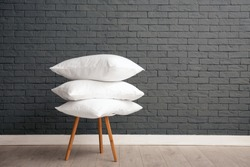 Pile of soft bed pillows on chair near brick wall with space for text