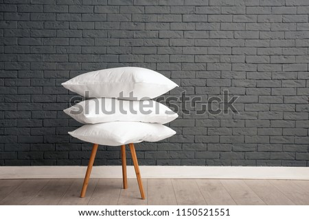 Pile of soft bed pillows on chair near brick wall with space for text ストックフォト ©