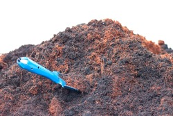 Pile of soil and coconut dust with a blue shovel isolated on white background.